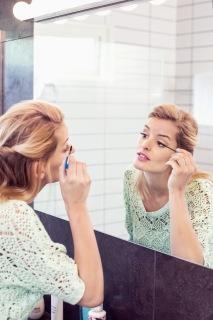 Ung kvinna sätter på mascara i badrum